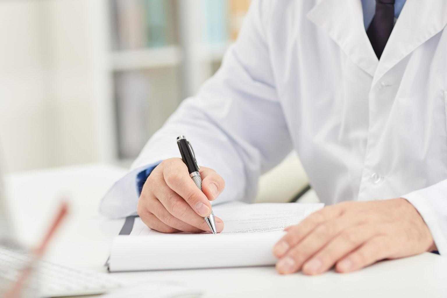 Close-up of male doctor in white coat sitting at the table and doing paper work at office